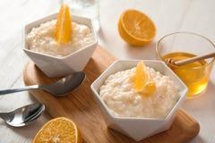 Le riz au lait crémeux avec les tranches oranges dans des cuvettes a servi image libre de droits