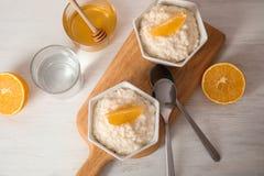 Le riz au lait crémeux avec les tranches oranges dans des cuvettes a servi image stock