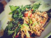 Le riz avec du porc et le basilic avec le vintage filtrent, foyer sélectif Image stock
