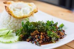 Le riz a complété avec l'oeuf au plat et le porc et le basilic faits sauter à feu vif Image stock
