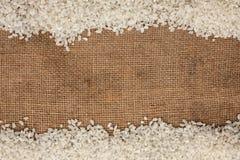 Le riz a dispersé sur la toile de jute Photographie stock libre de droits