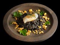 Le riz noir a fait cuire avec l'encre de seiches, et a fait frire calamar Photo libre de droits