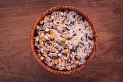 Le riz thaïlandais traditionnel de grain entier mélangé dans la cuillère et la cuvette soit Photo stock