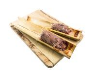 Le riz visqueux a rôti dans les joints en bambou (Khoalam) d'isolement sur le blanc Photos stock
