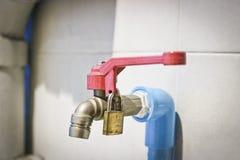 Le robinet avec de l'eau potable, la valve rouge est fermé pour fermer à clef Concept de consommation d'eau photos libres de droits