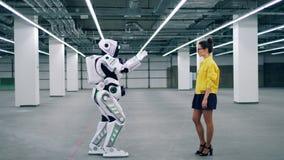 Le robot bionique et une jeune dame touchent les mains de chacun clips vidéos