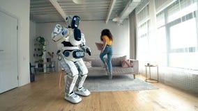 le robot comme humaine et une femme dansent et sautent banque de vidéos