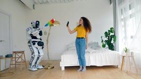 le robot comme humaine nettoie tandis qu'une dame s'amuse banque de vidéos