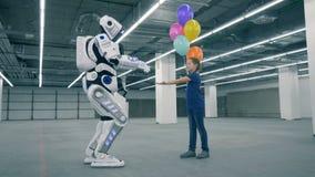 Le robot donne des ballons à une fille et puis touche sa main clips vidéos