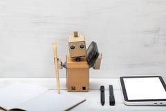 Le robot fonctionne, parlant au téléphone et écrit dans un carnet Image libre de droits