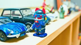 Le robot se tient devant sa voiture bleue photo stock