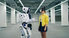 Le robot touche une main d'une dame en VR-verres banque de vidéos