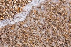 Le rocce e la spiaggia di pietra modellano il primo piano, fondo del litorale dell'estate Immagine Stock