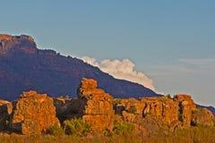 Le rocce nella sera si accendono con la montagna e la nuvola Immagini Stock Libere da Diritti