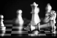 Le roi dans le support de jeu d'échecs de bataille sur l'échiquier avec l'OIN noire Photos libres de droits