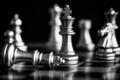 Le roi dans le support de jeu d'échecs de bataille sur l'échiquier avec l'OIN noire Image libre de droits