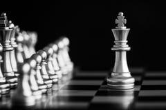 Le roi dans le support de jeu d'échecs de bataille sur l'échiquier avec l'OIN noire Photographie stock libre de droits