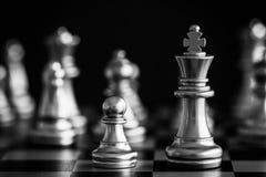Le roi dans le support de jeu d'échecs de bataille sur l'échiquier avec l'OIN noire Photo stock
