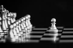 Le roi dans le support de jeu d'échecs de bataille sur l'échiquier avec l'OIN noire Image stock