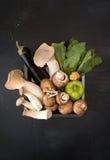 Le roi de champignons d'huître répand et des légumes sur le backgroun foncé Image stock