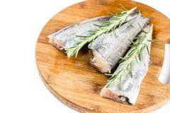 Le romarin frais s'embranche sur les poissons crus de merluches Photo libre de droits