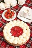 Le rond doux a fait le gâteau cuire au four avec des fraises sur le rouge image libre de droits