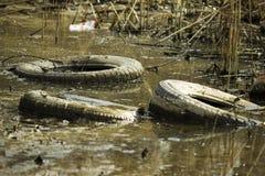 Le rond noir a jeté des pneus de dessous le mensonge de voiture au fond d'un étang vert photographie stock libre de droits