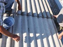Le Roofer Repair et remplacent de vieilles tuiles de toit d'amiante dangereux Images stock