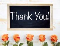 Le rose arancio e la lavagna nera con le parole vi ringraziano Fotografia Stock Libera da Diritti