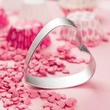 Le rose arrose sous forme de mensonge de coeur sur la surface et forme en métal d'un aloyau pour un biscuit Images libres de droits