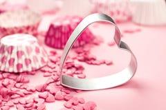 Le rose arrose sous forme de mensonge de coeur sur la surface et forme en métal d'un aloyau pour un biscuit, une image abstraite  Images libres de droits