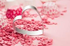 Le rose arrose sous forme de mensonge de coeur sur la surface et forme en métal d'un aloyau pour un biscuit, une image abstraite  Images stock