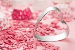 Le rose arrose sous forme de mensonge de coeur sur la surface et forme en métal d'un aloyau pour un biscuit, une image abstraite  Image libre de droits