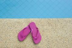 Le rose chausse près de l'eau bleue de la piscine Photographie stock libre de droits