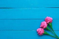 Le rose fresche fiorisce nel raggio di luce su fondo di legno dipinto turchese Fuoco selettivo Posto per testo immagine stock