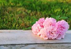 Le rose fresche rosa fiorisce sulla tavola di legno rustica all'aperto Immagini Stock