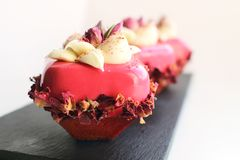 Le rose a monté des desserts de bouquet avec les fleurs comestibles crèmes et sèches du plat foncé images libres de droits