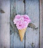 Le rose rosa fiorisce in cono gelato su fondo di legno rustico Fotografie Stock