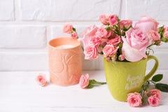 Le rose rosa fiorisce in tazza e nella candela verdi contro il mattone bianco Immagini Stock