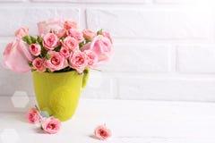 Le rose rosa fiorisce in tazza verde contro il muro di mattoni bianco Immagine Stock Libera da Diritti