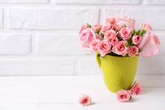 Le rose rosa fiorisce in tazza verde contro il muro di mattoni bianco Fotografia Stock