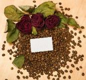 Le rose rosse asciutte e la carta in bianco rivestono sui semi del caffè e sul fondo di legno Fotografie Stock