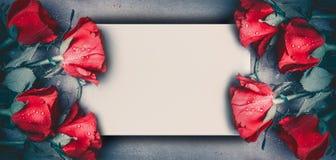 Le rose rosse deridono sull'insegna su fondo da tavolino grigio, vista superiore Disposizione per il giorno di biglietti di S. Va fotografia stock