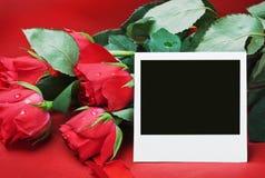 Le rose rosse e la foto incorniciano un testo di congratulazioni Fotografia Stock