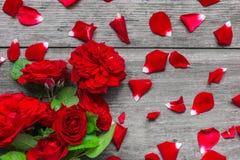 Le rose rosse fiorisce il mazzo con i petali sopra la tavola di legno rustica Immagini Stock