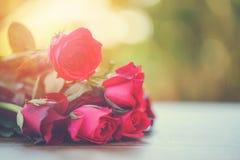 Le rose rose rouge de bouquet de fleur et les roses rouges aiment le jour en bois de valentines de fond de nature de table pour l image stock
