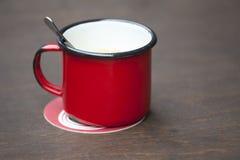 Le rouge a émaillé la tasse sur une table en bois Photo libre de droits