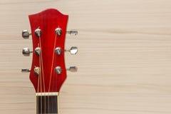 Le rouge acoustique de guitare, le cou se trouve sur la musique espagnole de mur de fond de lumière et rectangulaire classique en Photo stock