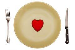 Le rouge, coeur de jouet est d'un plat vert avec des couverts Image stock