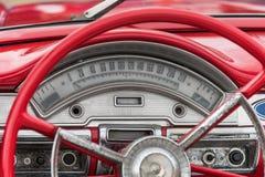 Le rouge a coloré de vieux détails, roue et tachymètre américains de voiture Photos stock